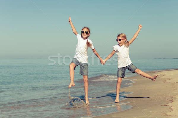 Dos hermanas jugando playa día tiempo Foto stock © altanaka
