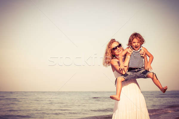 Mother and son playing on the beach at the day time. Stock photo © altanaka