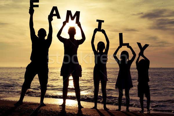 счастливая семья Постоянный пляж закат время письма Сток-фото © altanaka