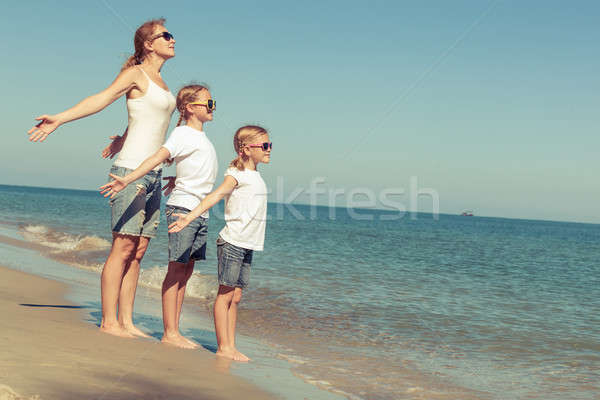 Mother and daughters  playing on the beach at the day time. Stock photo © altanaka