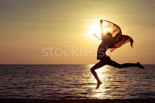счастливая девушка прыжки пляж закат время женщину Сток-фото © altanaka