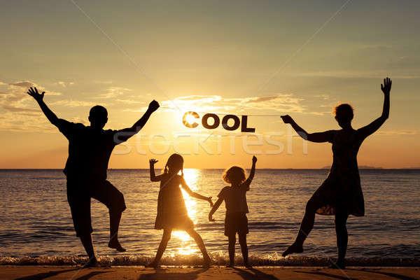 ストックフォト: 幸せな家族 · 立って · ビーチ · 日没 · 時間 · 両親