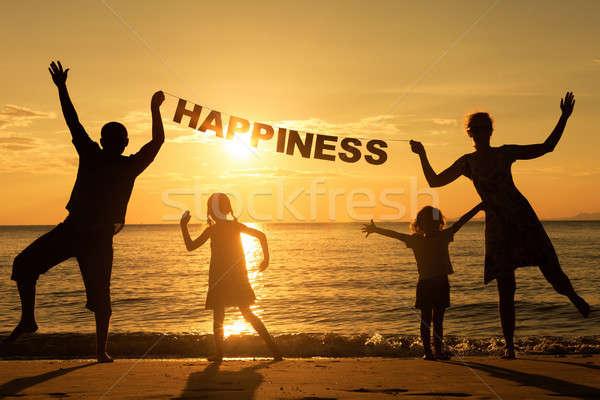 Happy family standing on the beach Stock photo © altanaka