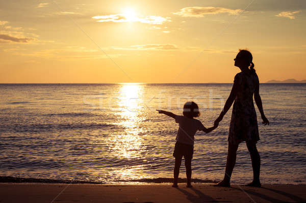 Mother and son playing on the beach at the sunset time. Stock photo © altanaka