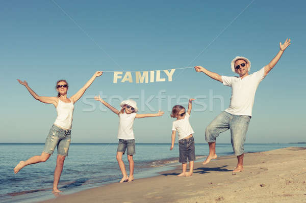 Happy family standing on the beach at the day time. Stock photo © altanaka