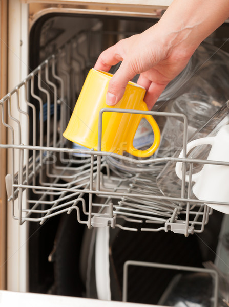 Hand putting a mug into a dishwasher Stock photo © Amaviael