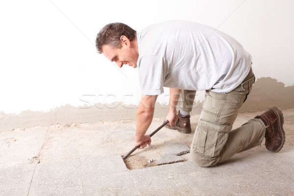 Manual worker disassembling old floor tiles Stock photo © Amaviael