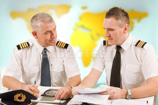 Airline pilots filling in papers in ARO Stock photo © Amaviael