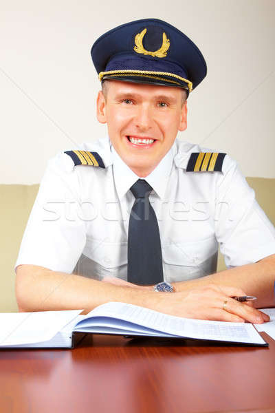 Airline pilot filling in papers in ARO Stock photo © Amaviael