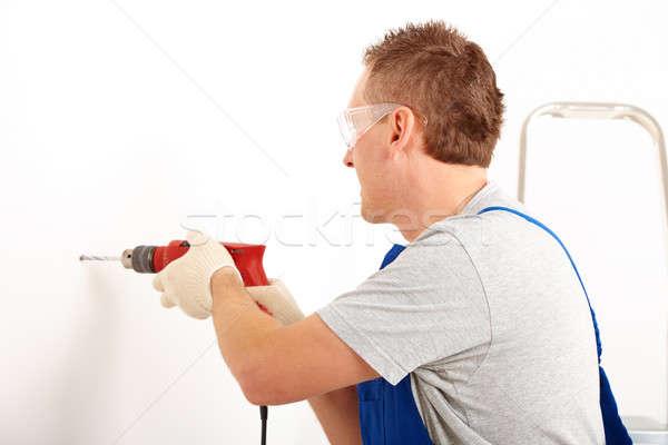 Hombre perforación agujero de trabajo blanco pared Foto stock © Amaviael