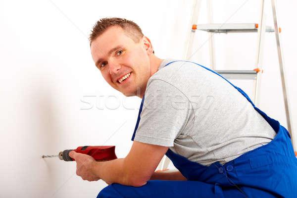 Férfi fúrás lyuk derűs dolgozik fehér Stock fotó © Amaviael