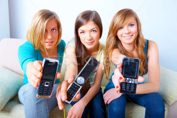 три девочек Мобильные телефоны красивой сидят диван Сток-фото © Amaviael