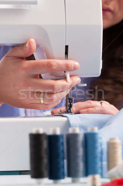 Hands on sewing machine with reels of colour threads and sewing  Stock photo © Amaviael