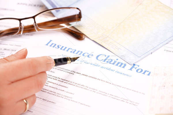 Stock photo: hand filling in insurance claim form