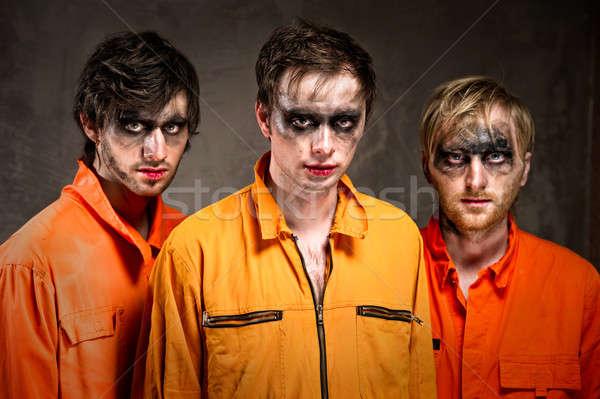 Three criminals in orange uniforms indoors  Stock photo © amok