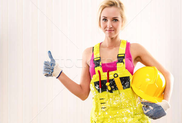 Woman in coverall holding hard hat and showing thumbs up Stock photo © amok