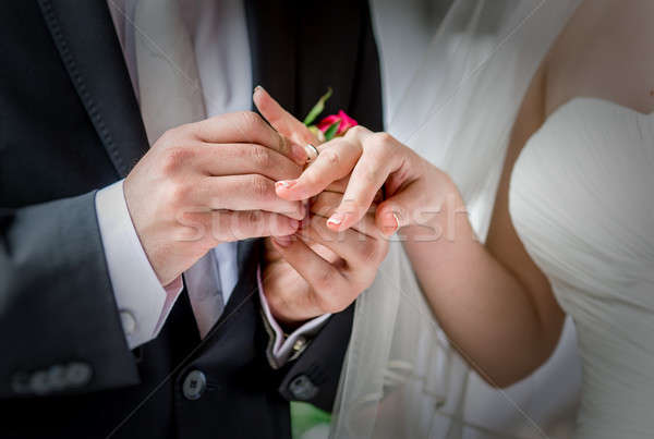 Groom placing a wedding ring on the finger of his bride  Stock photo © amok