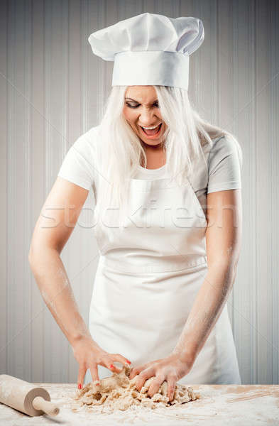 Angry and stressed out woman cook kneading dough Stock photo © amok