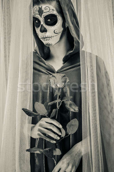 Day of the dead girl with sugar skull makeup holding rose Stock photo © amok