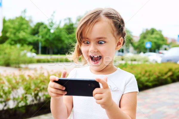 Adorable expressive little girl with a smartphone outdoors Stock photo © amok