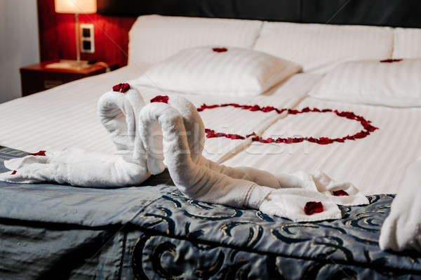Honeymoon bed decorated with red rose petals and towels Stock photo © amok
