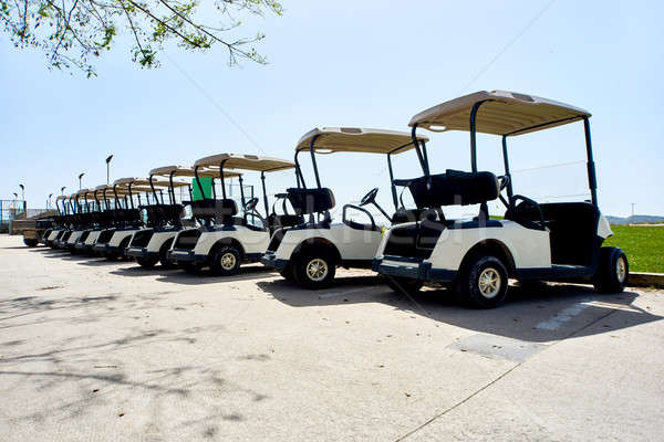Stock photo: Golf cars or golf carts in a row outdoors on a sunny spring day