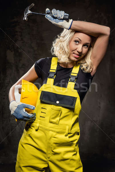 Tired builder woman with hammer and helmet indoors Stock photo © amok