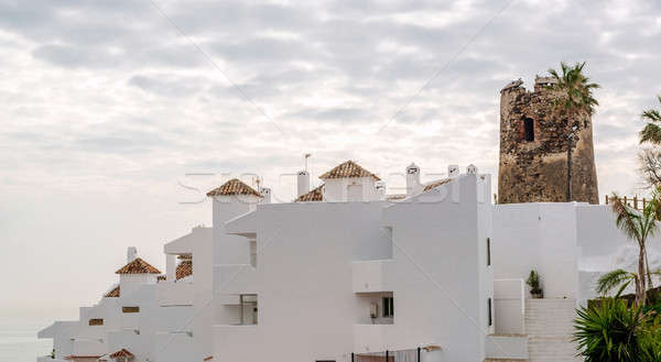 Rooftops of the spanish condominium and tower against cloudy sky Stock photo © amok