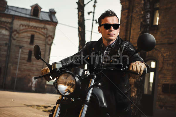 Man sitting on a cafe-racer motorcycle outdoors Stock photo © amok