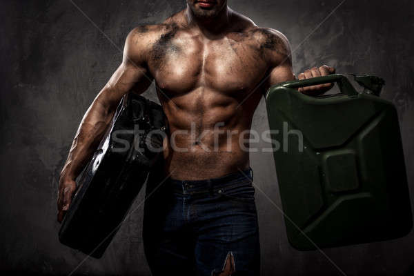 Muscular man with two metal fuel cans indoors Stock photo © amok