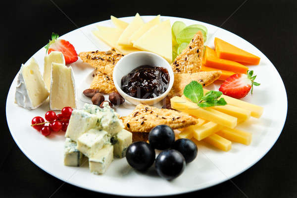 Platter with different types of cheese, fresh fruits and sauce Stock photo © amok