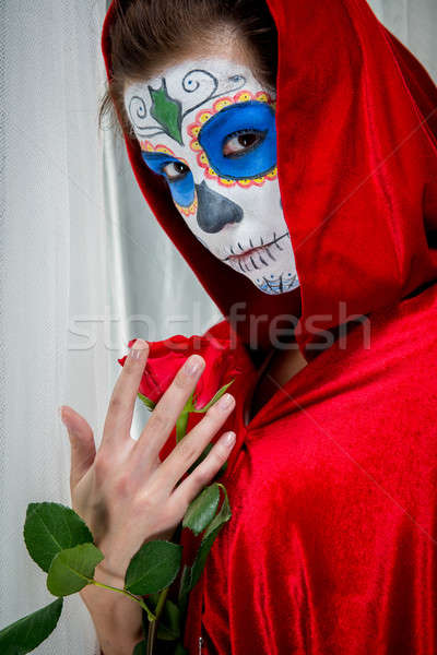 Day of the dead girl with sugar skull makeup holding red rose Stock photo © amok