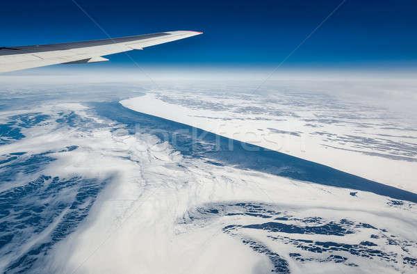 Wing of airplane flying above the Sea of Okhotsk Stock photo © amok