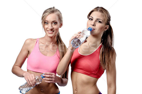 Two beautiful young women drinking water after fitness exercise Stock photo © amok