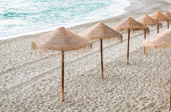 Straw parasols on empty beach. Nerja, Spain Stock photo © amok
