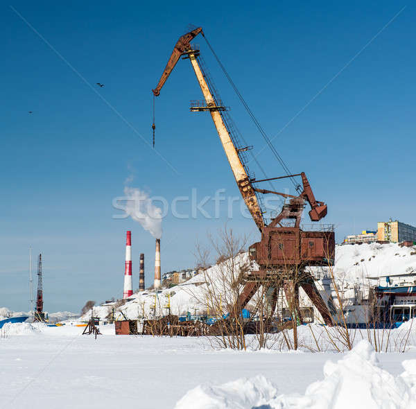 Stock photo: Old crane on Ship graveyard and power plants on a background