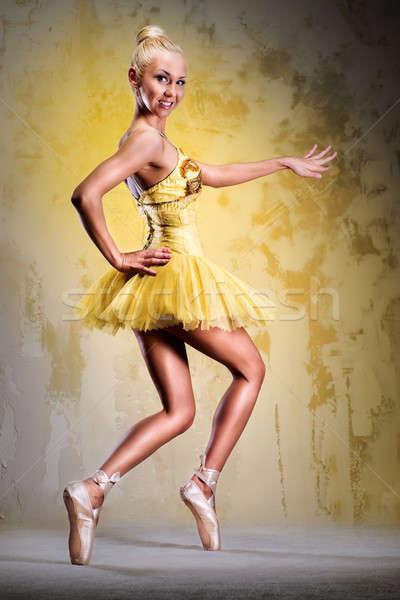 Beautiful ballerina in yellow tutu on point posing over obsolete wall Stock photo © amok