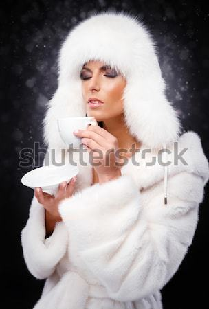 Bela mulher branco casaco de pele boné potável café Foto stock © amok