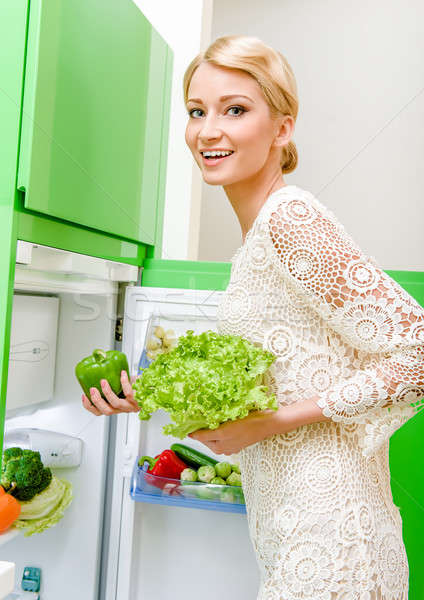 Smiling young woman taking vegetables out of fridge Stock photo © amok