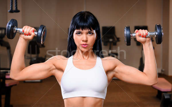 Beautiful young woman working out in fitness club Stock photo © amok