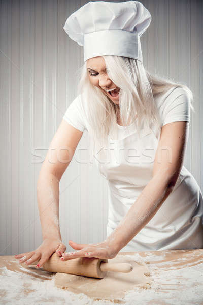 Angry and stressed out woman cook rolling dough Stock photo © amok