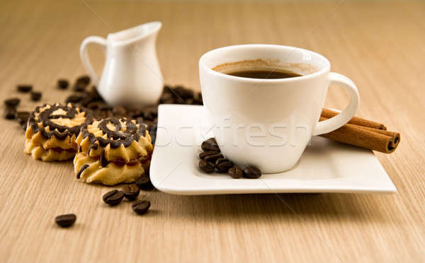 Cup of coffee with beans and cinnamon sticks over wooden backgro Stock photo © amok