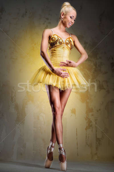 Beautiful ballerina in yellow tutu on point over obsolete wall Stock photo © amok