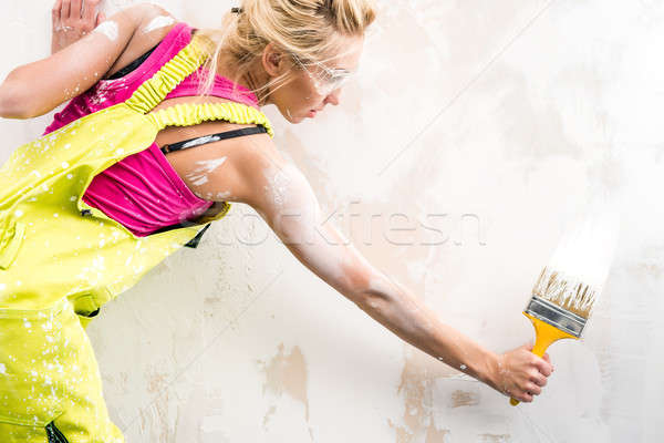 Female worker in coverall paint a  wall Stock photo © amok