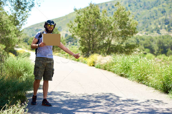 Hitch-hiking traveler with a blank cardboard sign Stock photo © amok