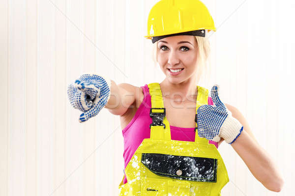 Woman in coverall and hard hat showing thumbs up indoors Stock photo © amok