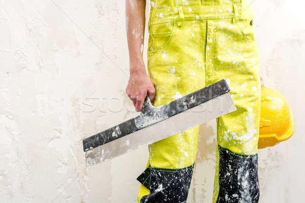 Construction worker with putty knife over obsolete background Stock photo © amok