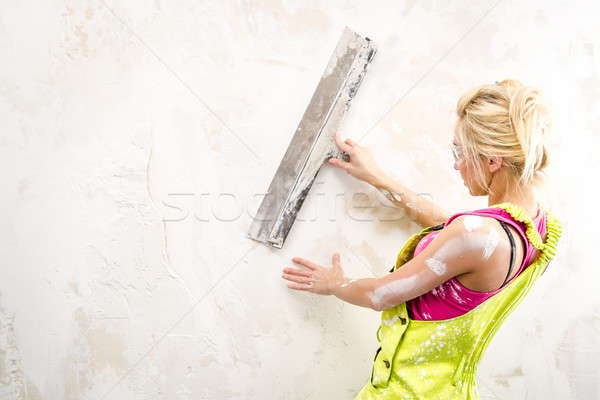 Female with putty knife working indoors Stock photo © amok