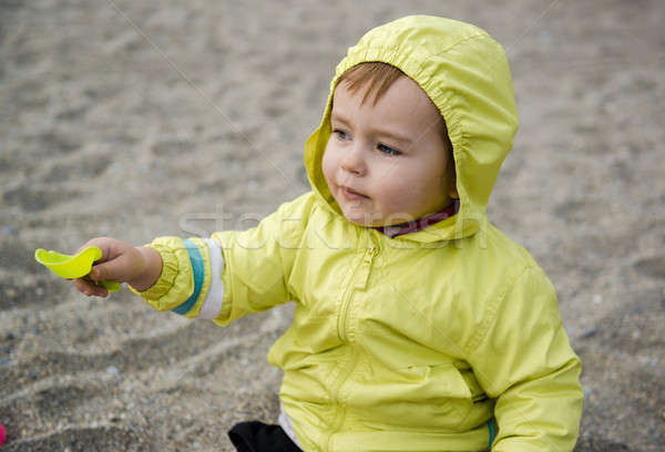Lovely baby girl playing with plastic shovel on the beach Stock photo © amok