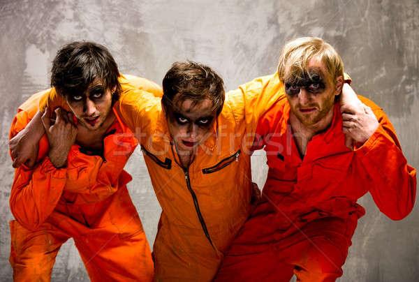 Three guys in orange uniforms indoors Stock photo © amok